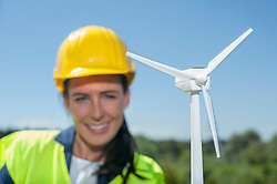Female engineer with wind turbine at geothermal power station, Bavaria, Germany