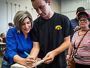 "15 JUNE 2019 - BOONE, IOWA: US Senator JONI ERNST (R-IA) signs autographs at ""Joni's Roast and Ride,"" a motorcycle ride / fund raiser hosted by Ernst. Ernst, Iowa's junior US Senator, kicked off her re-election campaign during the ""Roast and Ride"", an annual fund raiser and campaign event has she held since originally being elected to the US Senate in 2014.   PHOTO BY JACK KURTZ"
