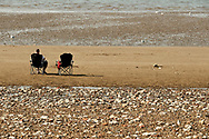 Two folding chair on the brach in Hunstanton, one occupied by a man the other left vacant with some items on it. Taken on the last hot day of the Summer in Hunstanton Norfolk, the first summer in the UK during the COVID-19 pandemic.<br /> <br /> Photo by Jonathan J Fussell, COPYRIGHT 2020