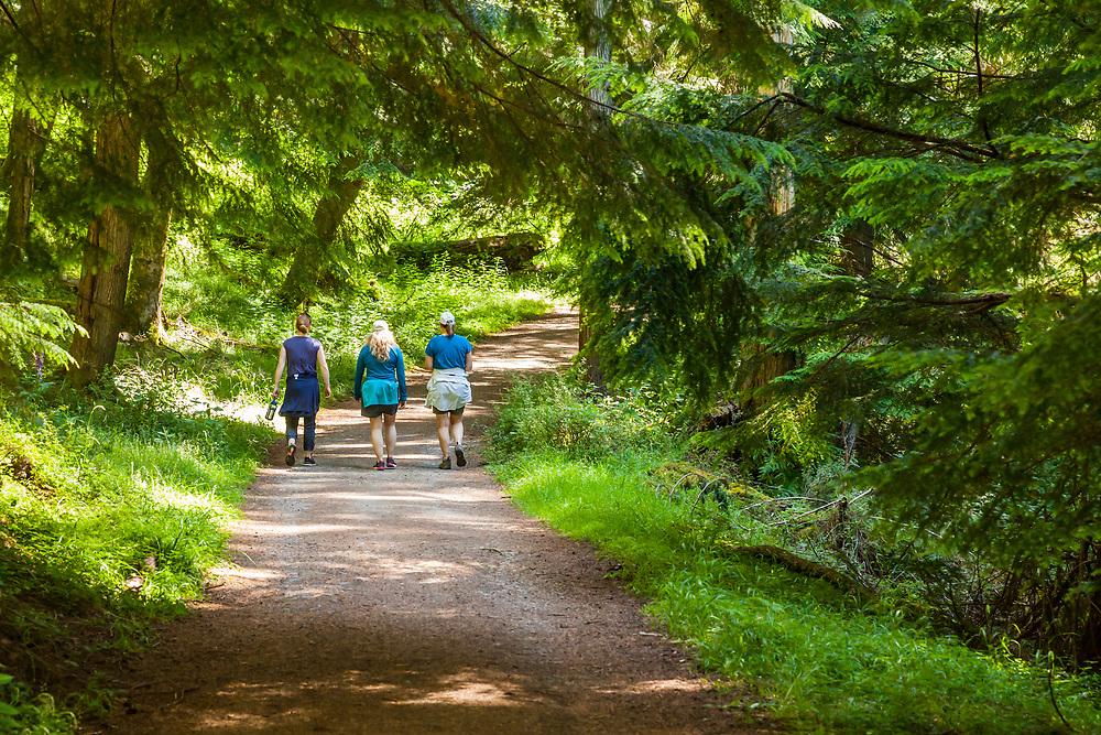Three women walk on the Cascade Creek Trail in Moran State Park, Orcas Island, Washington, USA.