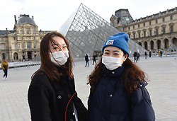 """Chinese tourists wear face mask near the Louvre Museum in Paris, France, on January 28, 2020. An elderly Chinese tourist in a """"serious condition"""" in a Paris hospital is France's fourth confirmed case of the new coronavirus that has killed more than 100 people since it emerged in the Chinese city of Wuhan, France's top health official said Tuesday. Photo by Alain Apaydin/ABACAPRESS.COM"""