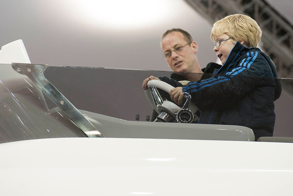 A father watches his son steer. The Sunseeker stand. The London Boat Show opens at the Excel Centre, Docklands, London, UK 04 January 2014. Guy Bell, 07771 786236, guy@gbphotos.com