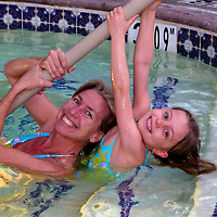 USA, California. Mother and daughter smiling in a swimming pool.