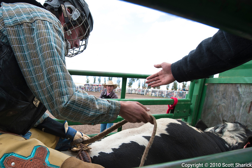 This bull rider gets a helping hand as he ties down in preparation of his imending death ride. Missoula Photographer, Missoula Photographers, Montana Pictures, Montana Photos, Photos of Montana