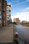 Historic industrial buildings and ship at low tide, River Hull, Hull, Yorkshire, England