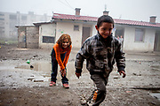 A boy and a girl playing a game with coins on a muddy patch of ground in the middle of the Roma settlement located in 'Budulovska street' in Moldava nad Bodvou (2012). The city has roughly 11200 inhabitants, about 1980 (18%) of them have Roma ethnicity and around 800 are living at the segregated settlement 'Budulovska Street' (2014).