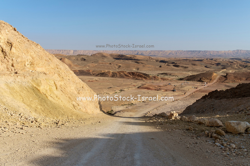 Dirt track through the  The Ramon Crater, The Ramon Crater is the world's largest karst erosion cirque. It is located at the peak of Mount Negev. The Ramon Crater is 40 kilometers long and 2 to 10 kilometers wide, shaped like an elongated heart.