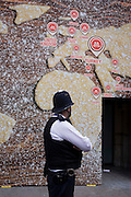 Police officer walks beneath a world map on a bakery business hoarding.
