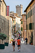 Couple walking in Via Ricasoli in old hill town of Montalcino, Val D'Orcia,Tuscany, Italy RESERVED USE - NOT FOR DOWNLOAD - FOR USE CONTACT TIM GRAHAM