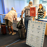 Volunteers from the Connecticut Department of Health ask passengers who arrive at Bradley International Airport if they have filled out their quarantine forms on Friday, July 31, 2020 in Windsor Locks, Connecticut. Per Governor Lamont's recent executive order,  passengers arriving from states with significant community spread of COVID-19 need to fill out a travel form and self-quarantine for 14 days or the length of their trip.  (Alex Menendez via AP)