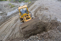 Heavy equipment works on a placer mine in the Klondike near Dawson City, Yukon