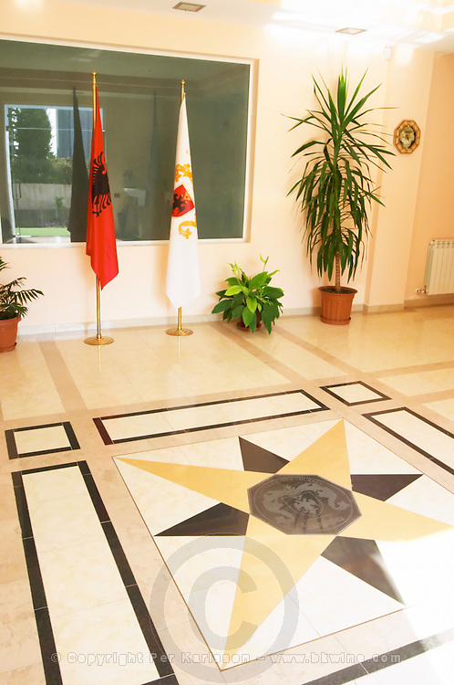 At the entrance to the winery, the Albanian flag and the flag of the winery. Star shaped pattern in the stone floor. Kantina e Pijeve Gjergj Kastrioti Skenderbeu Skanderbeg winery, Durres. Albania, Balkan, Europe.