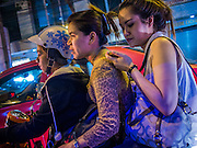 10 JANUARY 2014 - BANGKOK, THAILAND:   A woman on the back of a motorcycle checks her smart phone.    PHOTO BY JACK KURTZ