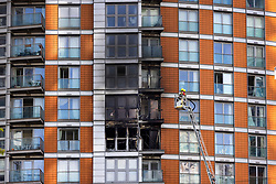 © Licensed to London News Pictures. 07/05/2021. London, UK. Fire fighters use a hoist to inspect the charred remains of apartments at New Providence Wharf in Poplar in east London. 100 fire fighters and 20 crews tackled the blaze at it's peak. Photo credit: Peter Macdiarmid/LNP