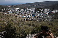 A man sitting on some rocks on the top of a hill overlooking the makeshift camp, in the backdrop Turkey. About 20000 are living in a makeshift camp nearby the city of Moria on the island of Lesbos in miserable conditions, most of the without water, electricity nor sanitary facilities.  Federico Scoppa