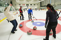 Kim Conrad (in white) from team Broom Broom Pow reacts as her stone is bumped by the Four Sheets to the Wind team's players Chris Miller, Phil Swanson and Rita Seto during Thursday night Curling League at Plymouth State University's Ice Arena.   (Karen Bobotas/for the Laconia Daily Sun)
