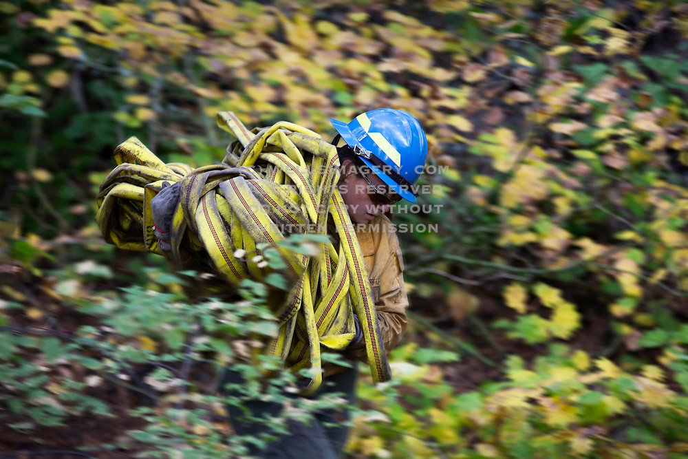 Image of a female firefighter prepping her hoses in rural Washington state, Pacific Northwest by Randy Wells
