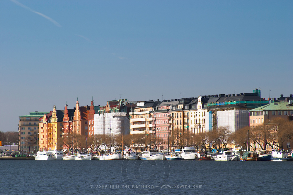 View over the Riddarfjarden bay of lake Malaren to Norrmalarstrand, fashionable waterfront residential area with colourful buildings and old ships docked at the key. Kungsholmen Stockholm. Sweden, Europe.