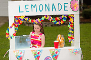 Rachel Mennet, a third-grader, stands behind her lemonade stand to raise money for wounded warrior Nick Bailley and his dog Abel on September 23, 2014 in Summerville, South Carolina.