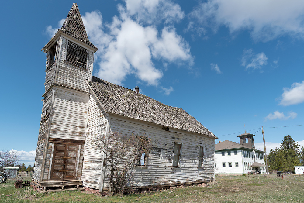Old leaning church and school in the ghost town of Flora, Oregon