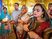 "09 SEPTEMBER 2013 - BANGKOK, THAILAND:  Indian women pray during Ganesha Chaturthi celebrations at Shiva Temple in Bangkok. Ganesha Chaturthi also known as Vinayaka Chaturthi, is the Hindu festival celebrated on the day of the re-birth of Lord Ganesha, the son of Shiva and Parvati. The festival, also known as Ganeshotsav (""Festival of Ganesha"") is observed in the Hindu calendar month of Bhaadrapada. The date usually falls between 19 August and 20 September. The festival lasts for 10 days, ending on Anant Chaturdashi. Ganesha is a widely worshipped Hindu deity and is revered by many Thai Buddhists. Ganesha is widely revered as the remover of obstacles, the patron of arts and sciences and the deva of intellect and wisdom.    PHOTO BY JACK KURTZ"