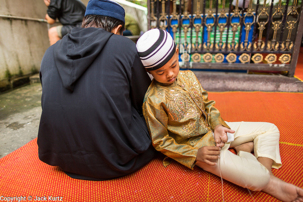"""08 AUGUST 2013 - BANGKOK, THAILAND: A boy rests on his father before Eid al-Fitr services at Haroon Mosque in Bangkok. Eid al-Fitr is the """"festival of breaking of the fast,"""" it's also called the Lesser Eid. It's an important religious holiday celebrated by Muslims worldwide that marks the end of Ramadan, the Islamic holy month of fasting. The religious Eid is a single day and Muslims are not permitted to fast that day. The holiday celebrates the conclusion of the 29 or 30 days of dawn-to-sunset fasting during the entire month of Ramadan. This is a day when Muslims around the world show a common goal of unity. The date for the start of any lunar Hijri month varies based on the observation of new moon by local religious authorities, so the exact day of celebration varies by locality.      PHOTO BY JACK KURTZ"""
