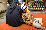 "08 AUGUST 2013 - BANGKOK, THAILAND: A boy rests on his father before Eid al-Fitr services at Haroon Mosque in Bangkok. Eid al-Fitr is the ""festival of breaking of the fast,"" it's also called the Lesser Eid. It's an important religious holiday celebrated by Muslims worldwide that marks the end of Ramadan, the Islamic holy month of fasting. The religious Eid is a single day and Muslims are not permitted to fast that day. The holiday celebrates the conclusion of the 29 or 30 days of dawn-to-sunset fasting during the entire month of Ramadan. This is a day when Muslims around the world show a common goal of unity. The date for the start of any lunar Hijri month varies based on the observation of new moon by local religious authorities, so the exact day of celebration varies by locality.      PHOTO BY JACK KURTZ"
