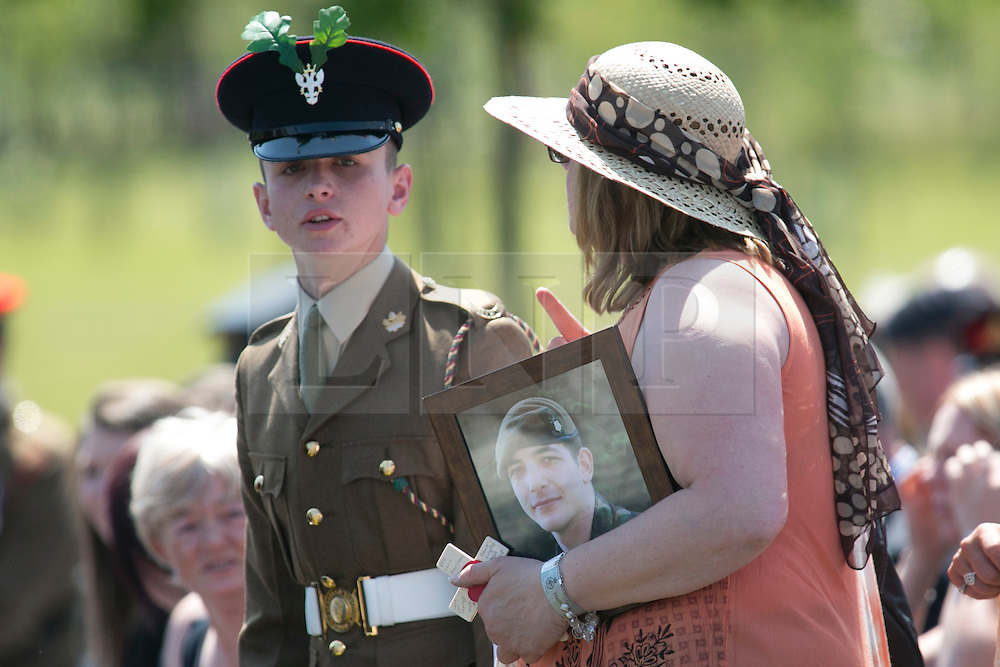© Licensed to London News Pictures. 11/06/2015. National Memorial Arboretum, Alrewas, Staffordshire, UK. The service to mark the Rededication of the Bastion Memorial. The memorial was begun in Helmand Province in 2006, deconstructed in 2014 and now replicated at the National Memorial Arboretum in Staffordshire. Around two thousand people took part in the service including HRH Prince Harry, the Prime Minister David Cameron and senior members of the Armed Forces. Pictured, guests take teir seats for the service. Photo credit : Dave Warren/LNP
