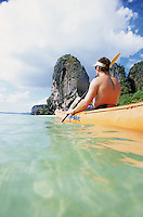 A young man paddles a sea kayak on the Andaman Sea in Thailand.