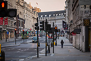 A lone pedestrian walks down an eerily quiet Regent Street on what would normally be the evening rush hour in London on March 27th, 2020. The centre of London is extremely quiet with almost every business closed and very few people about because of the Governments lockdown measures due to the Coronavirus crisis.