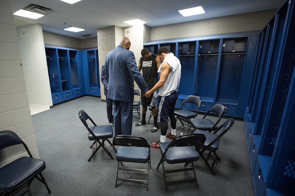 Former NBA player Andrew Lang, who is the chaplain for the Atlanta Hawks, prays with Brooklyn Nets' Cory Jefferson (center) and the Atlanta Hawks' John Jenkins during a service before an NBA Playoff game on Wednesday, April 22, 2015 at Philips Arena in Atlanta. Photo by Kevin Liles for The New York Times