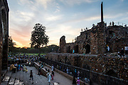 """19th March 2015, New Delhi, India. Dusk view of the three-tiered arcaded pavilion with an Ashokan Pillar atop it in the ruins of Feroz Shah Kotla in New Delhi, India on the 19th March 2015<br /> <br /> PHOTOGRAPH BY AND COPYRIGHT OF SIMON DE TREY-WHITE a photographer in delhi<br /> + 91 98103 99809. Email: simon@simondetreywhite.com<br /> <br /> People have been coming to Firoz Shah Kotla to leave written notes and offerings for Djinns in the hopes of getting wishes granted since the late 1970's. Jinn, jann or djinn are supernatural creatures in Islamic mythology as well as pre-Islamic Arabian mythology. They are mentioned frequently in the Quran  and other Islamic texts and inhabit an unseen world called Djinnestan. In Islamic theology jinn are said to be creatures with free will, made from smokeless fire by Allah as humans were made of clay, among other things. According to the Quran, jinn have free will, and Iblīs abused this freedom in front of Allah by refusing to bow to Adam when Allah ordered angels and jinn to do so. For disobeying Allah, Iblīs was expelled from Paradise and called """"Shayṭān"""" (Satan).They are usually invisible to humans, but humans do appear clearly to jinn, as they can possess them. Like humans, jinn will also be judged on the Day of Judgment and will be sent to Paradise or Hell according to their deeds. Feroz Shah Tughlaq (r. 1351–88), the Sultan of Delhi, established the fortified city of Ferozabad in 1354, as the new capital of the Delhi Sultanate, and included in it the site of the present Feroz Shah Kotla. Kotla literally means fortress or citadel."""