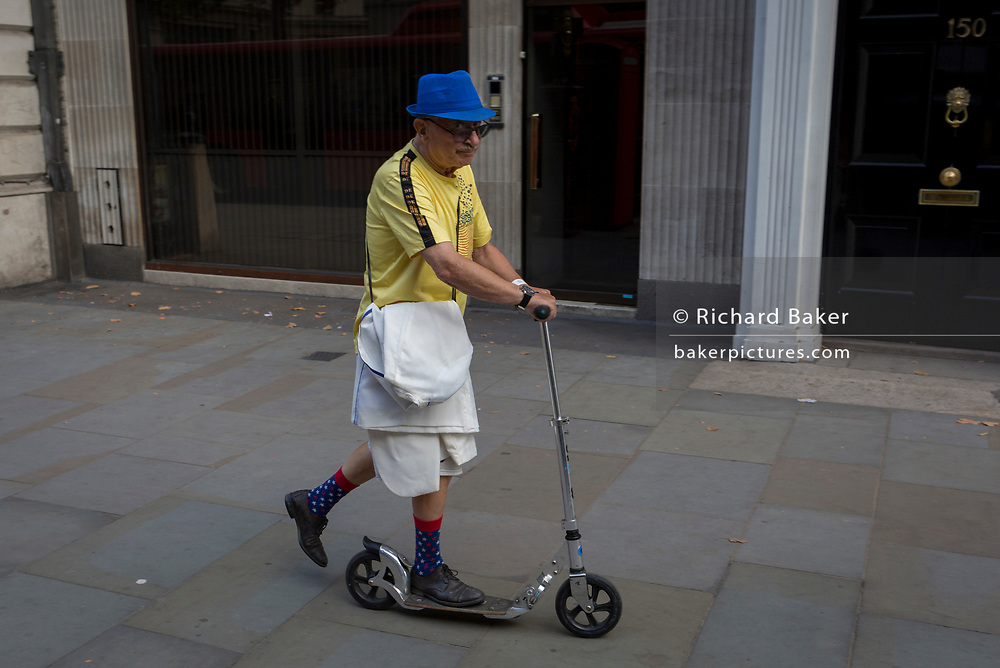 An eccentric elderly gentleman rides his scooter along the Strand, on 1st September 2017, in London, England.