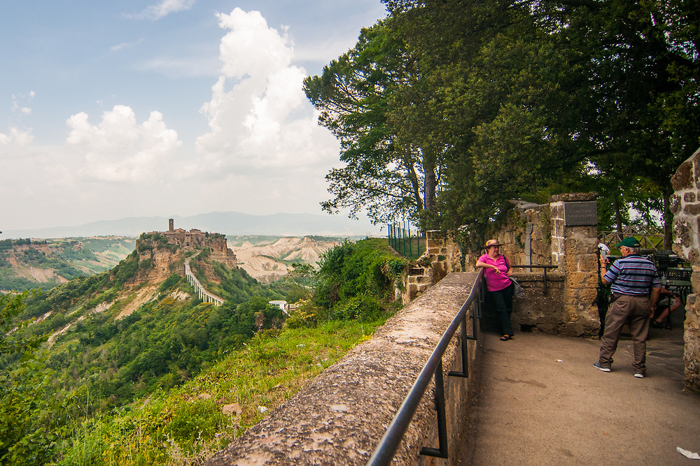 """Tourists take a picture at the panoramic terrace at Civita di Bagnoregio.<br /> Civita di Bagnoregio is a town in the Province of Viterbo in central Italy, a suburb of the comune of Bagnoregio, 1 kilometre (0.6 mi) east from it. It is about 120 kilometres (75 mi) north of Rome. Civita was founded by Etruscans more than 2,500 years ago. Bagnoregio continues as a small but prosperous town, while Civita became known in Italian as La città che muore (""""The Dying Town""""). Civita has only recently been experiencing a tourist revival. The population today varies from about 7 people in winter to more than 100 in summer.The town was placed on the World Monuments Fund's 2006 Watch List of the 100 Most Endangered Sites, because of threats it faces from erosion and unregulated tourism."""