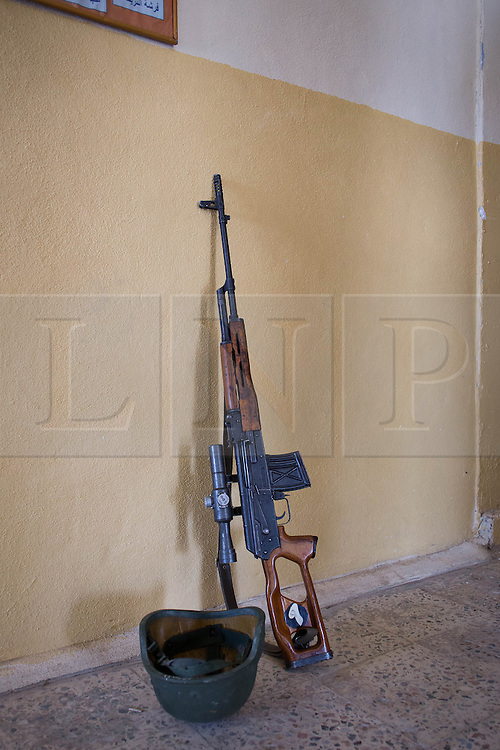 © Licensed to London News Pictures. 29/06/2014. Khanaqin, UK 29/06/2014. Khanaqin, Iraq. The sniper rifle of a Kurdish peshmerga leans against a wall in their barracks in Khanaqin, Iraq, after troops returned from fighting with ISIS insurgents in nearby Jalawla.  Counted by Kurds as part of their homeland, fighting in the town of Jalawla now consists of occasional skirmishes and exchanges of fire between snipers and heavy machine guns on both sides.<br /> <br /> The peshmerga, roughly translated as those who fight, is at present engaged in fighting ISIS all along the borders of the relatively safe semi-automatous province of Iraqi-Kurdistan. Though a well organised and experienced fighting force they are currently facing ISIS insurgents armed with superior armament taken from the Iraqi Army after they retreated on several fronts.. Photo credit : Matt Cetti-Roberts/LNP