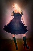 Digitally enhanced image of a female model wearing lolita style dress with high heeled boots