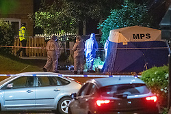 © Licensed to London News Pictures. 19/05/2020. London, UK. Forensic investigators stand next to a police tent on Wiltshire Gardens. Police were called at 20:22BST to reports of shots fired in Wiltshire Gardens in Haringey. Metropolitan Police Service attended along with London Ambulance Service and found a man, believed to be aged in his 20s, suffering gunshot injuries. The man was pronounced dead at the scene. Photo credit: Peter Manning/LNP