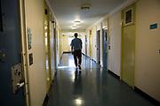 A prisoner walking down the enhanced wing corridor. HMP/YOI Portland, Dorset. A resettlement prison with a capacity for 530 prisoners. Dorset, United Kingdom.