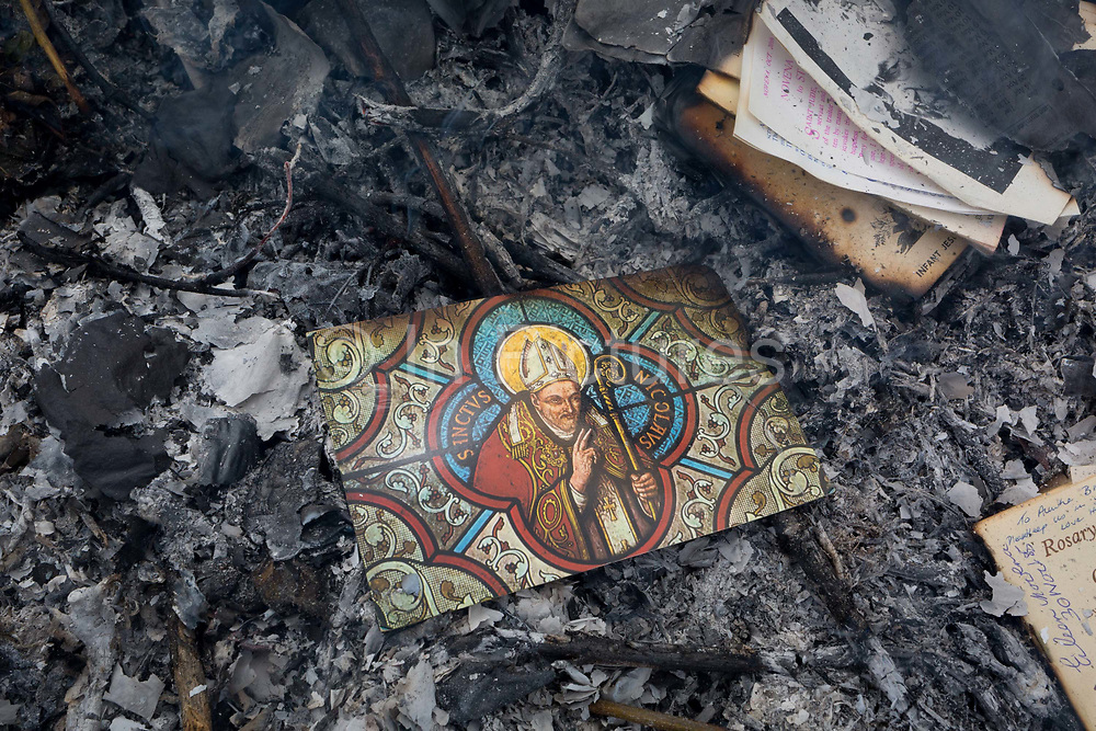 A postcard of patron Saint Nicholas, all that is left after the burning on a bonfire of religious mementoes, personal data, accounts records and general paperwork, on 30th July 2017, in Wrington, North Somerset, England. Saint Nicholas 270 – 343AD, was an historic 4th-century Christian saint.