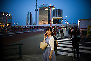 TOKYO, JAPAN, 5 MAY - Asakusa - A woman take a phone call - in the back ground is the achitectural complex of Asahi biru - beer compagny, on the left, the building of Philippe Starck- and in the back ground the Tokyo Sky Tree. May 2012