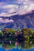Phewa Lake in Pokhara, Western Region, Nepal with 22,943 foot Machapuchare (aka Fish Tail), in the Annapurna Range of the Himalayas, peering out above. The mountain is revered by the local population as particularly sacred to the god Shiva, and hence is off limits to climbing.