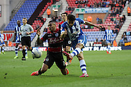 Wigan Athletic's Jordi Gomez gets his shot away under pressure from Queens Park Rangers Danny Simpson. Skybet football league championship play off semi final, 1st leg match, Wigan Athletic v QPR at the DW Stadium in Wigan, England on Friday 9th May 2014.<br /> pic by Chris Stading, Andrew Orchard sports photography.