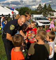 Chief Chris Adams talks with Calvin Hobbs, Jayden Allen, Jeremy Hodges and Dominik Allen during Laconia's National Night Out at Blueberry Lane Apartments on Tuesday evening.   (Karen Bobotas/for the Laconia Daily Sun)