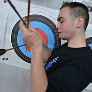 "NORTH YARMOUTH, Maine,  -- 1/17/16 --  Dakota Butte, 16, of Jefferson, Maine pulls his arrows out of the target at Lakeside Archery in North Yarmouth as part of the 10th Fire & Ice Burn Survivors Winter Camp put on by the Portland Firefighters Children's Burn Foundation. Portland area firefighters served as camp counselors - bringing child victims of burn trauma to the Camden Snow Bowl, Lakeside Archery and several other regional locations for group events and personal support activities.  <br /> Fire and Ice started in 2005 with four burn victims and nine counselors. This year there were 23 youth campers from all over New England participating in a three-day event. Campers came together by doing series of activities in which they become close friends. ""These kids have all been through similar traumatic experiences,"" said Portland Firefighter and counselor Sheldon Gregiore.  <br /> A first-time youth camper (whose identity is being kept anonymous) said, ""All I can say is, burned people rule!""  <br /> For more information, register or donate visit: http://www.maineburnsurvivors.org. <br /> Photo © Roger S. Duncan 2016 for The Forecaster."