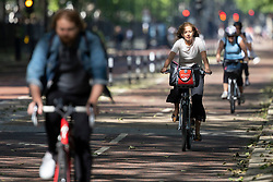 © Licensed to London News Pictures. 08/06/2021. London, UK. A woman cycles during sunny weather in St James's Park in Central London. Temperatures are expected to rise with highs of 23 degrees forecasted for parts of London and South East England today . Photo credit: George Cracknell Wright/LNP
