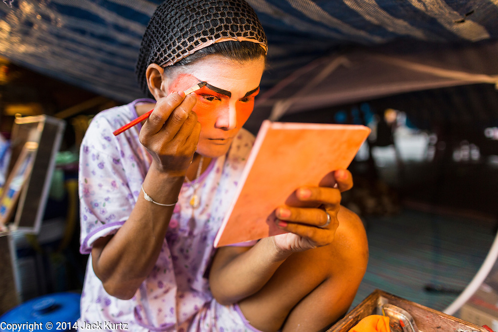 """19 AUGUST 2014 - BANGKOK, THAILAND:  A member of the Lehigh Leng Kaitoung Opera troupe applies her makeup before a performance at Chaomae Thapthim Shrine, a small Chinese shrine in a working class neighborhood of Bangkok. The performance was for Ghost Month. Chinese opera was once very popular in Thailand, where it is called """"Ngiew."""" It is usually performed in the Teochew language. Millions of Chinese emigrated to Thailand (then Siam) in the 18th and 19th centuries and brought their culture with them. Recently the popularity of ngiew has faded as people turn to performances of opera on DVD or movies. There are still as many 30 Chinese opera troupes left in Bangkok and its environs. They are especially busy during Chinese New Year and Chinese holiday when they travel from Chinese temple to Chinese temple performing on stages they put up in streets near the temple, sometimes sleeping on hammocks they sling under their stage. Most of the Chinese operas from Bangkok travel to Malaysia for Ghost Month, leaving just a few to perform in Bangkok.            PHOTO BY JACK KURTZ"""