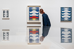 """© Licensed to London News Pictures. 13/07/2021. LONDON, UK. A staff member poses with (C) """"Coloured Gradation"""", 1939.  Preview of the first UK retrospective exhibition at Tate Modern of works by Sophie Taeuber-Arp (1889-1943), one of the foremost abstract artists and designers of the 1920s and 30s. Works from Taeuber-Arp's accomplished career as a painter, architect, teacher, writer, and designer of textiles, marionettes and interiors is on 15 July – 17 October 2021.   Photo credit: Stephen Chung/LNP"""