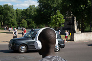 Young man listening to music on her headphones whilst travelling in London, United Kingdom.