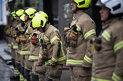 © Licensed to London News Pictures. 28/04/2020. London, UK. A firefighter bows his head during a minute silence at North Kensington Fire Station in Notting Hill, West London in honour of care workers who lost their lives in the fight against COVID-19. British Prime Minister Boris Johnson, who retuned to Downing Street on Monday, has warned the public against relaxing lockdown precautions too soon. Photo credit: Ben Cawthra/LNP