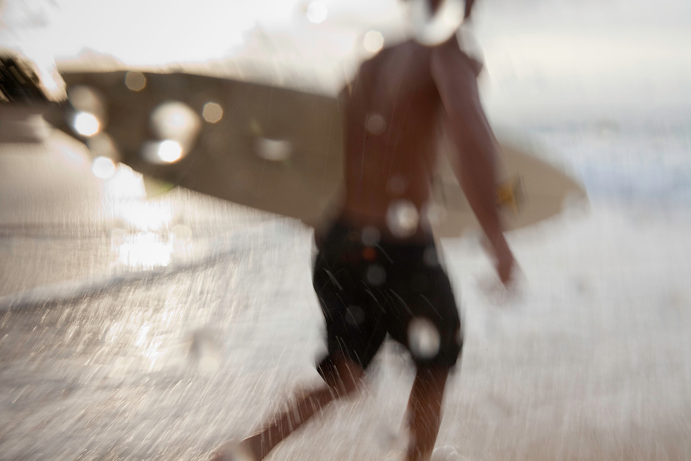 Surfer running into water at Sandy Beach